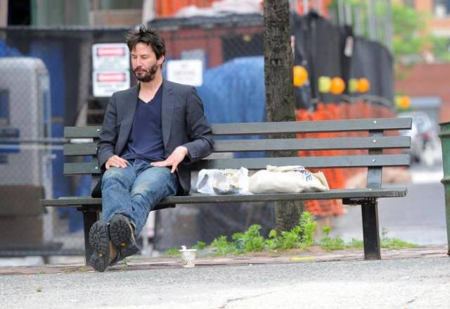 Keanu Reeves sitting on a bench