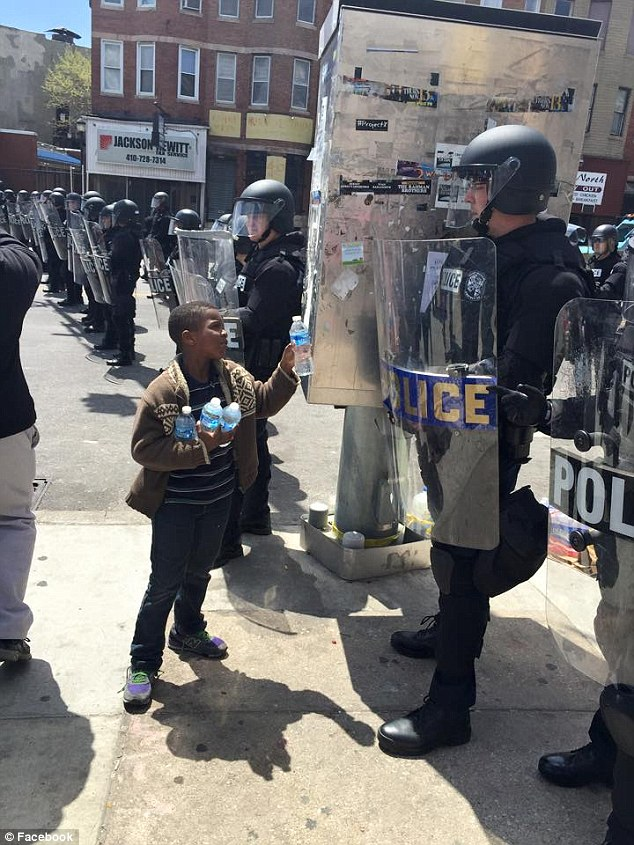 Act of kindness: This little boy was pictured handing out water bottles to police in Baltimore, Maryland on Tuesday, following a night of violent riots