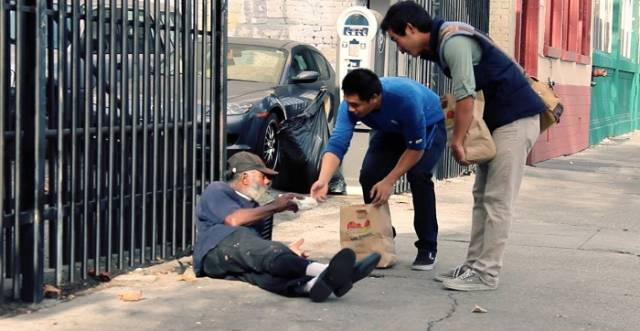 Giving food to homeless old man