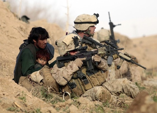 A soldier protects civilians in the front line.