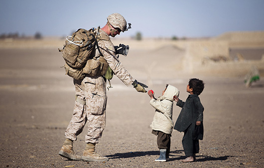 Soldier playing with kids