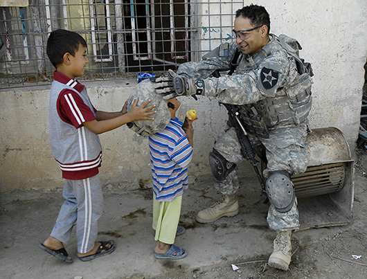 Soldier putting helmet on a kid
