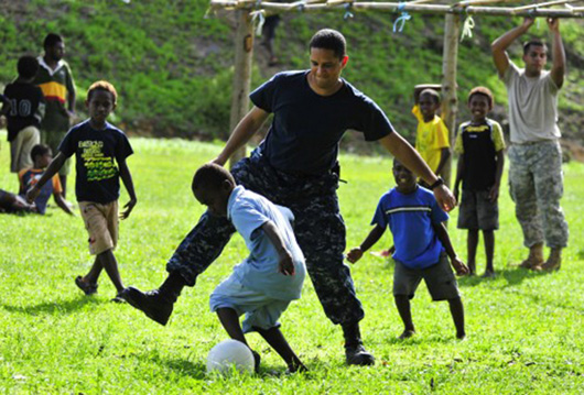 Soldier and kids playing sports.