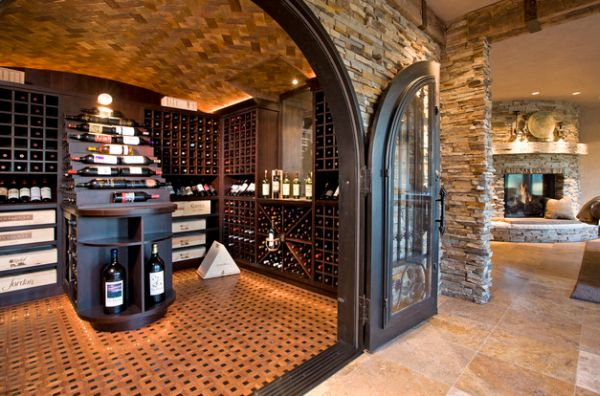 Large archway with iron doors and wooden flooring give this wine storage space a traditional look