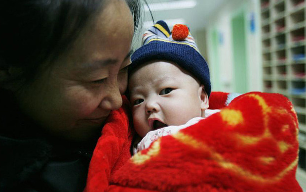 Li Lijuan holds one of her adopted babies