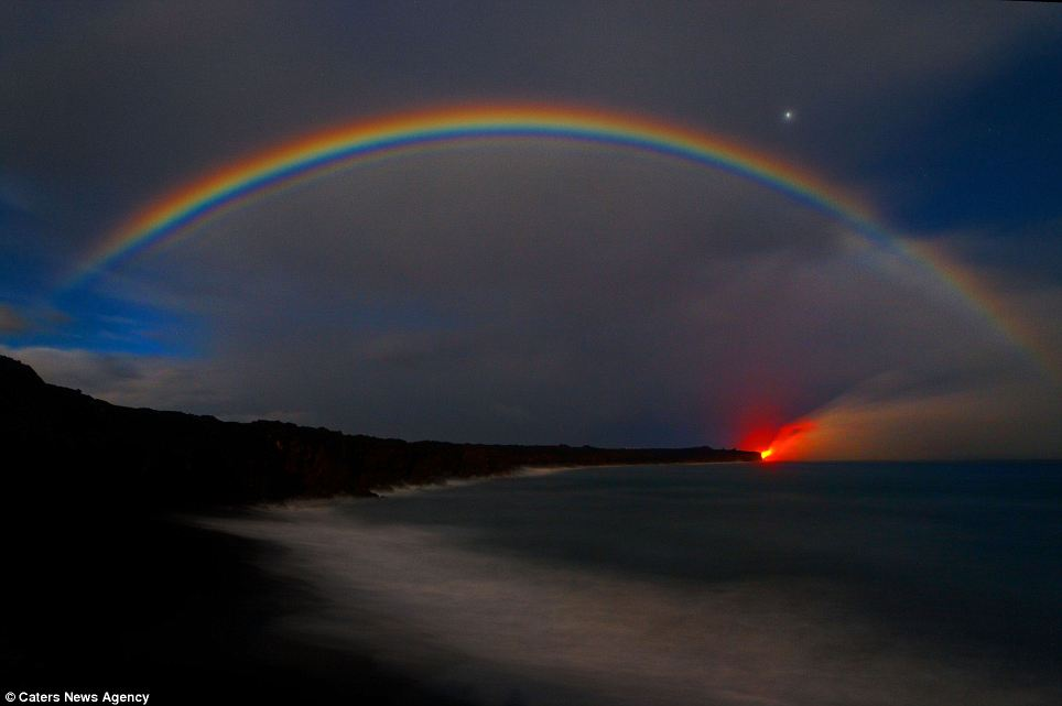 Stunning: The rising steam from the eruptions creates a rainbow across the evening sky