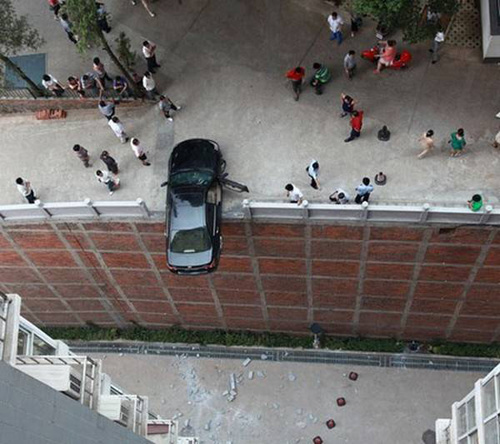 car dangles over edge; overhead view