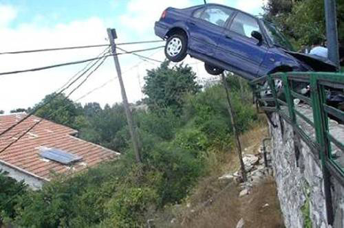 car dangles over rail by front tires