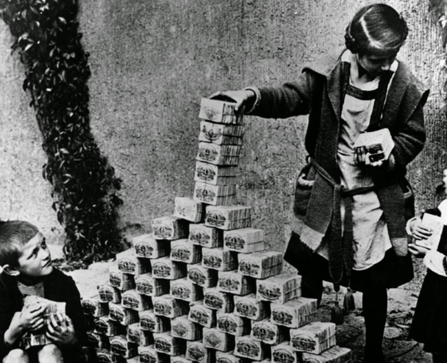 German children play with stacks of money during the hyperinflation period of the Weimar Republic, 1922.