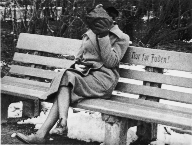 "A Jewish woman in Austria in 1938 sitting on a bench marked ""Only for Jews."""