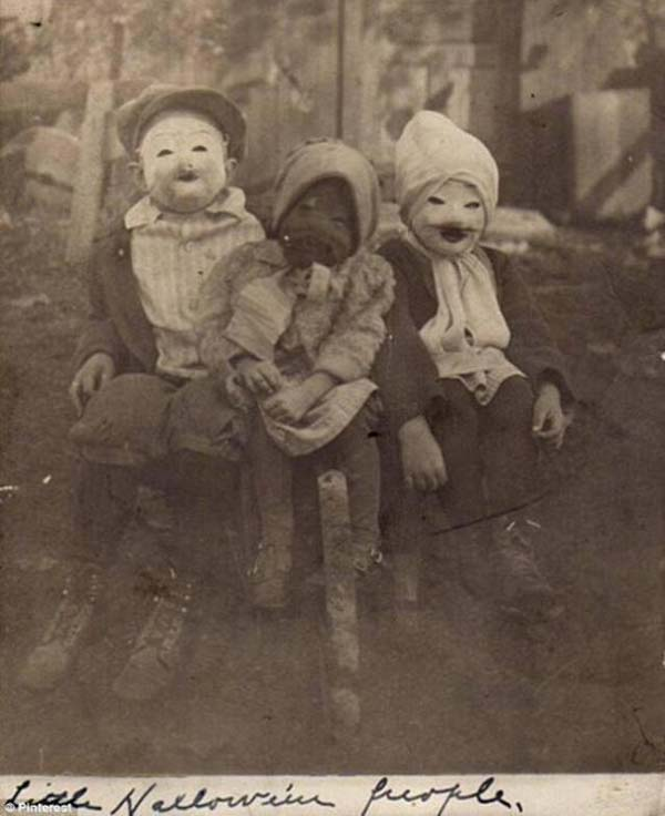 "Three kids and their spooky ""Halloween people"" costumes (1900)."