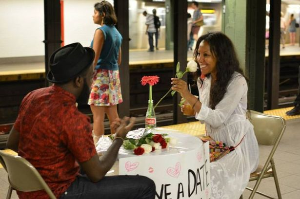 A woman smiles as she takes a flower on her 'date' on the New York subway