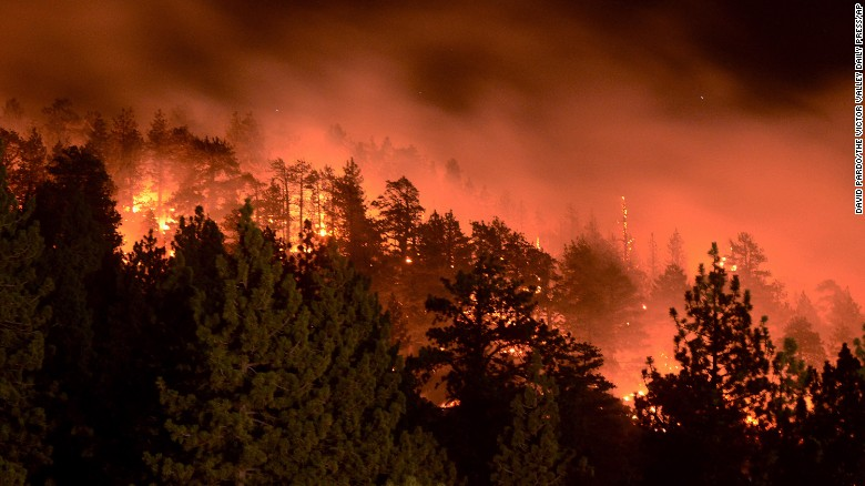 Flames from the Pines Fire burn on Saturday, July 18, in Wrightwood, California. The blaze was burning near Mount San Antonio, also called Mount Baldy for its snow-capped summit that's highly visible in the L.A. area.
