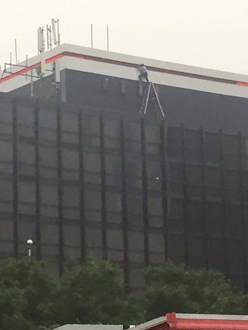 man on side of building on ladder