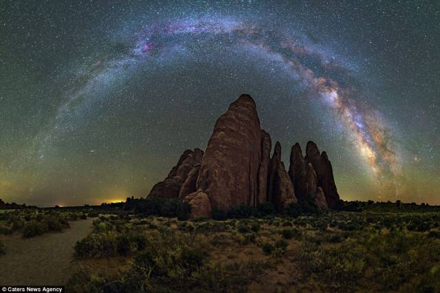 The towering rock formations in Arches National Park, Utah, stand tall below the disk-shaped galaxy that appears like a rainbow of the night
