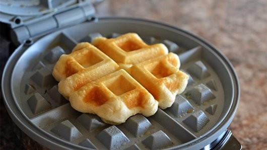 Place each biscuit into the center of the waffle iron and press. Cook for about three minutes, or until golden brown.