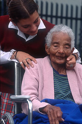 REACHING OUT: A volunteer helps a disabled and elderly person in Ecuador. (Photo: UNV)