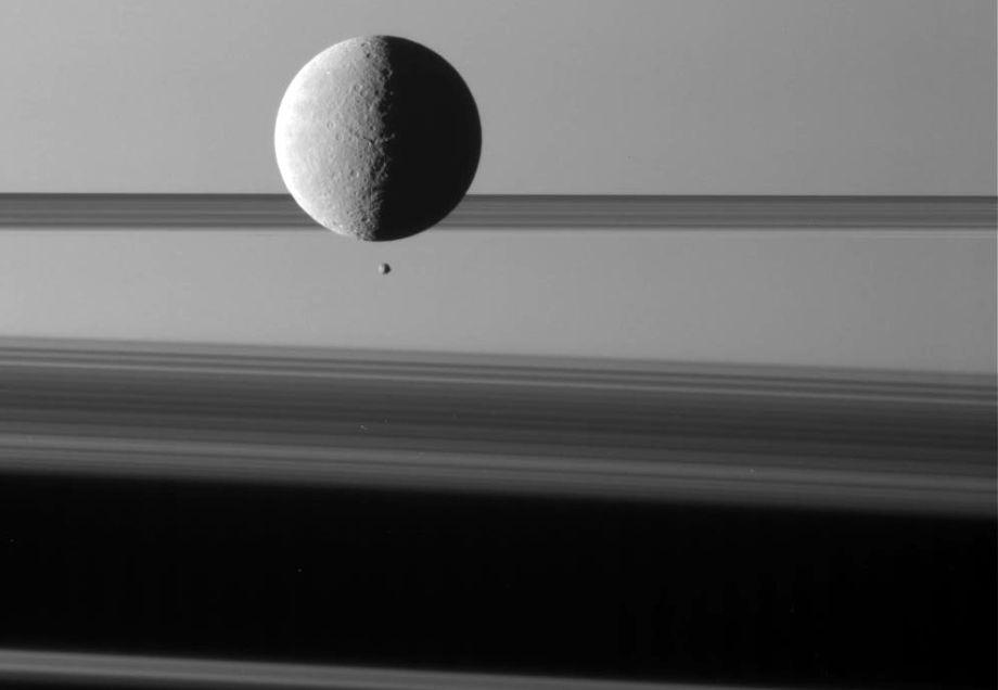 The moon Rhea looms near its sibling moon Epimetheus. Via Imgur