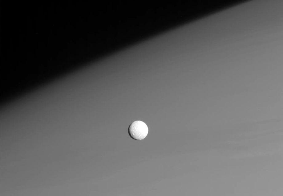 Mimas passes in front of Satrun's upper atmosphere.