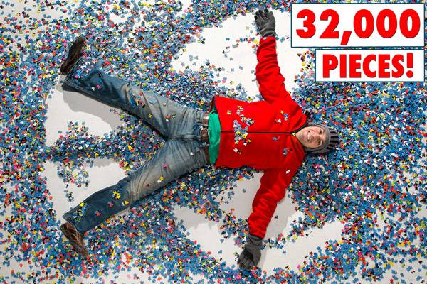 Man doing snow angels in the 32,000-piece World's Largest Puzzle.
