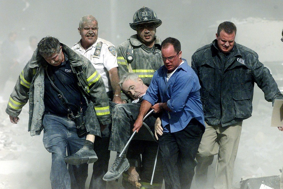 Sept. 11, 2001 — Workers carry FDNY chaplain Mychal Judge