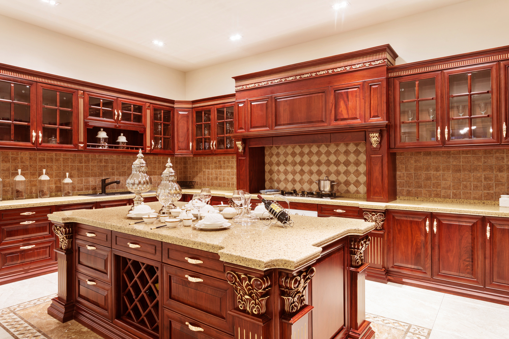 Red Toned Wood Kitchen Cabinets That Are Intricate In Design And Include  Many Glass